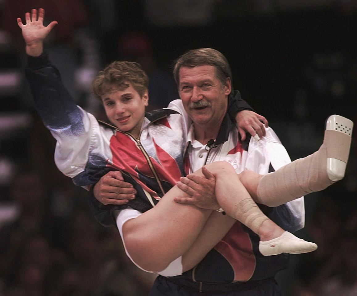 USA's Kerri Strug is carried by her coach, Bela Karolyi, as she waves to the crowd on her way to receiving her gold medal for the women's team gymnastics competition, at the Centennial Summer Olympic Games in Atlanta on Tuesday, July 23, 1996. Strug has two torn ligaments and a sprained ankle from the vault competition.  (AP Photo/Susan Ragan)