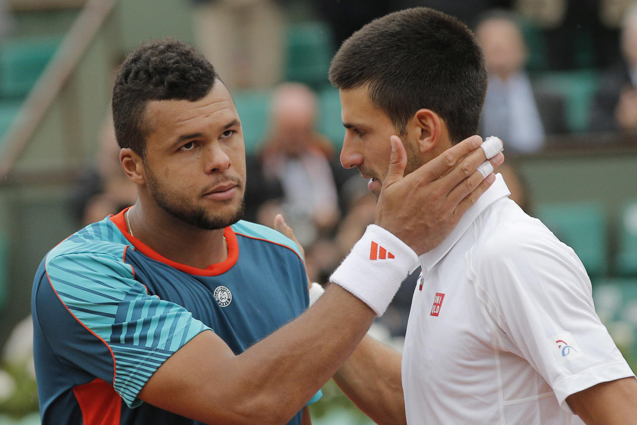 Jo-Wilfried Tsonga of France, left, congratulates Novak Djokovic of Serbia after losing his quarter final match at the French Open tennis tournament in Roland Garros stadium in Paris, Tuesday June 5, 2012. Djokovic won in five sets 6-1, 5-7, 5-7, 7-6, 6-1. (AP Photo/Christophe Ena)