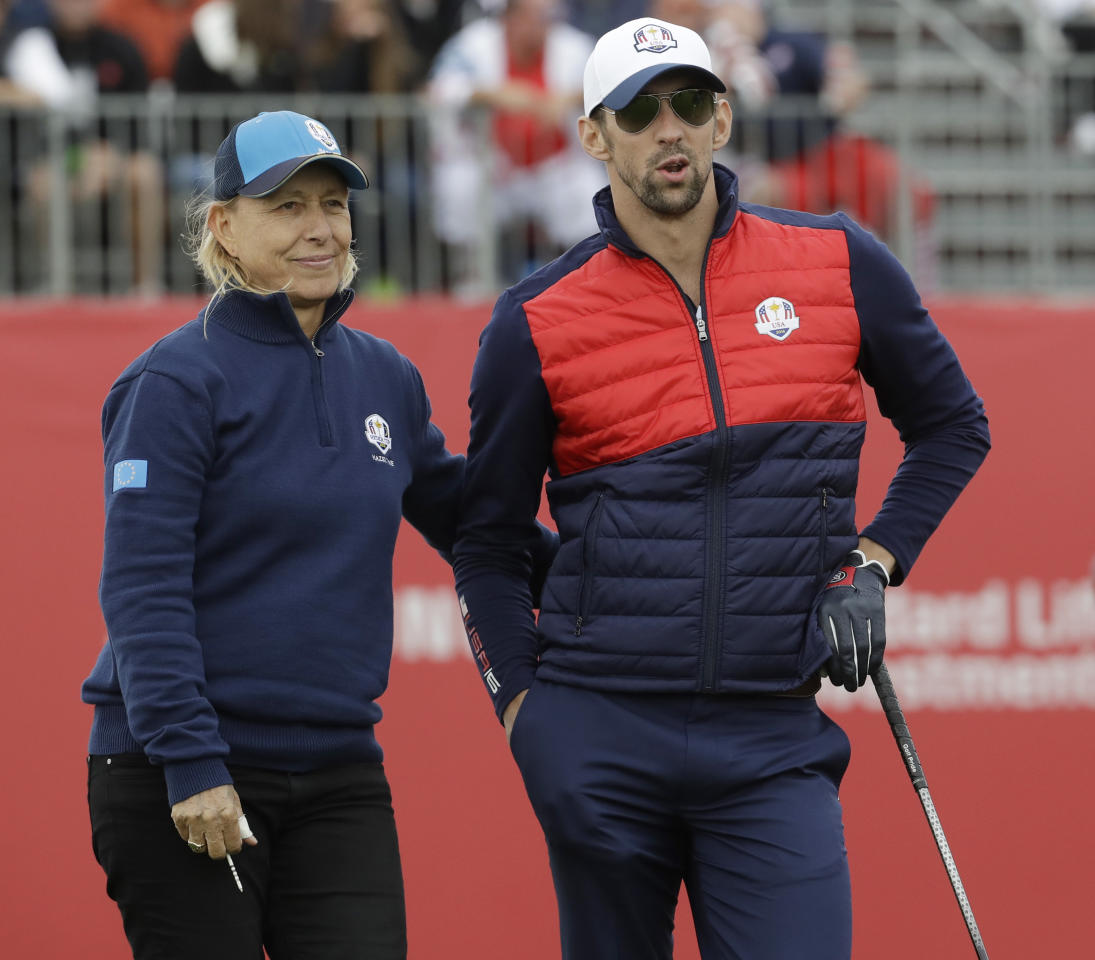 United States' Michael Phelps and Europe's Martina Narvratilova wait to tee off during the celebrity match at the Ryder Cup golf tournament Tuesday, Sept. 27, 2016, at Hazeltine National Golf Club in Chaska, Minn. (AP Photo/Chris Carlson)