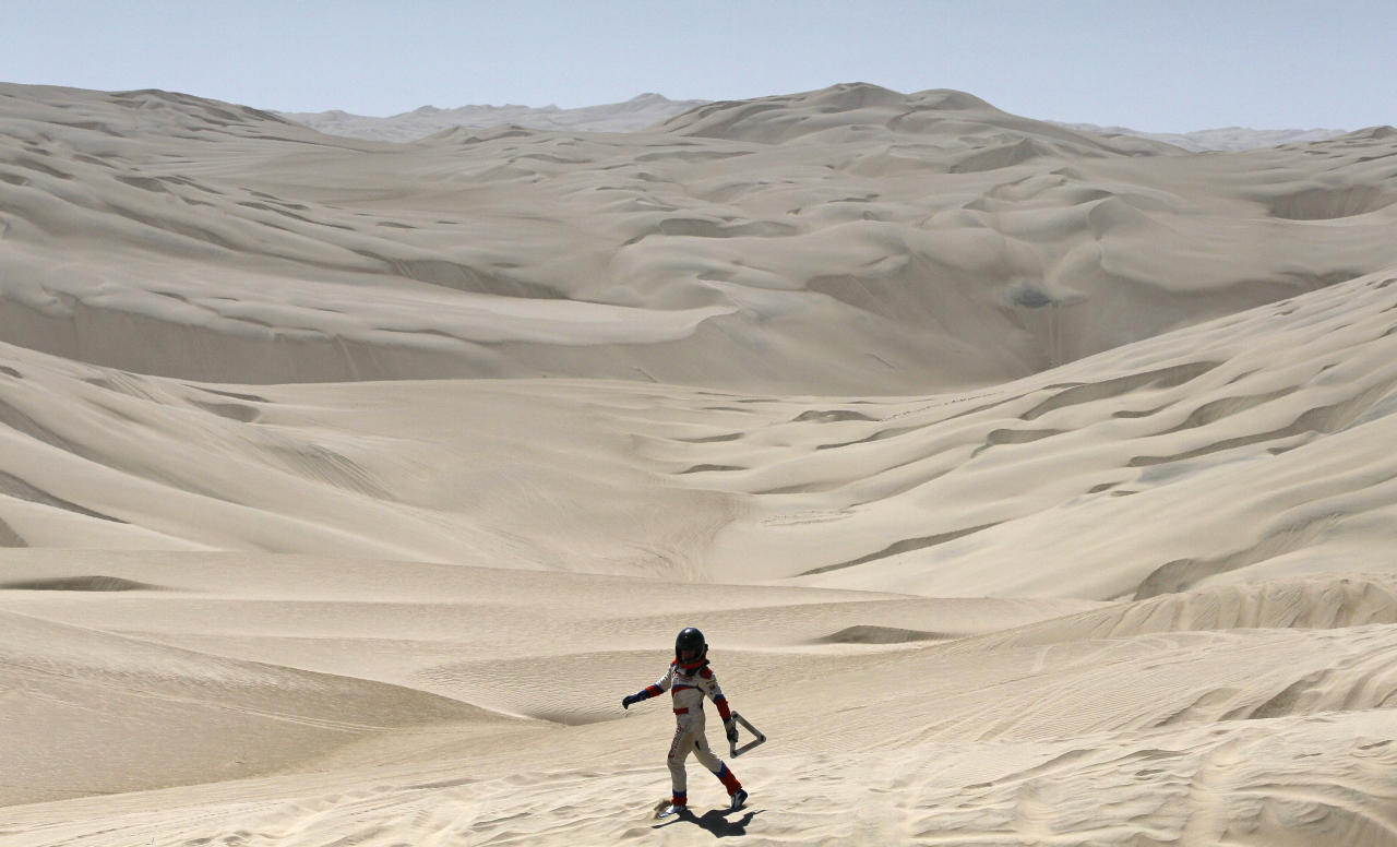 Erik Wevers, Dutch co-driver of the Mitsubishi driven by Fabian Lurquin, from Belgium, walks along the desert after their car got stuck in the sand during the 12th stage of the 2012 Argentina-Chile-Peru Dakar Rally between Arequipa and Nazca in Peru, Friday, Jan. 13, 2012. (AP Photo/Martin Mejia)