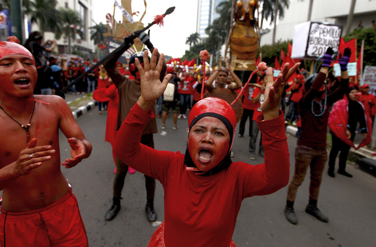 Indonesian workers painted in red chant slogans during a May Day rally in Jakarta, Indonesia, Wednesday, May 1, 2013. (AP Photo/Dita Alangkara)