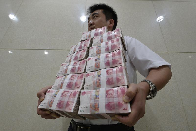 An employee carries bundles of 100 yuan Chinese bank notes after counting at a bank in Taiyuan