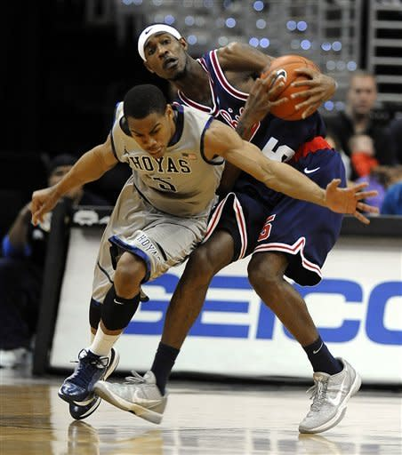Georgetown guard Markel Starks, left, tries to steal the ball from Memphis guard Will Barton (5) during second half of an NCAA college basketball game Thursday, Dec. 22, 2011, in Washington. (AP Photo/Richard Lipski)