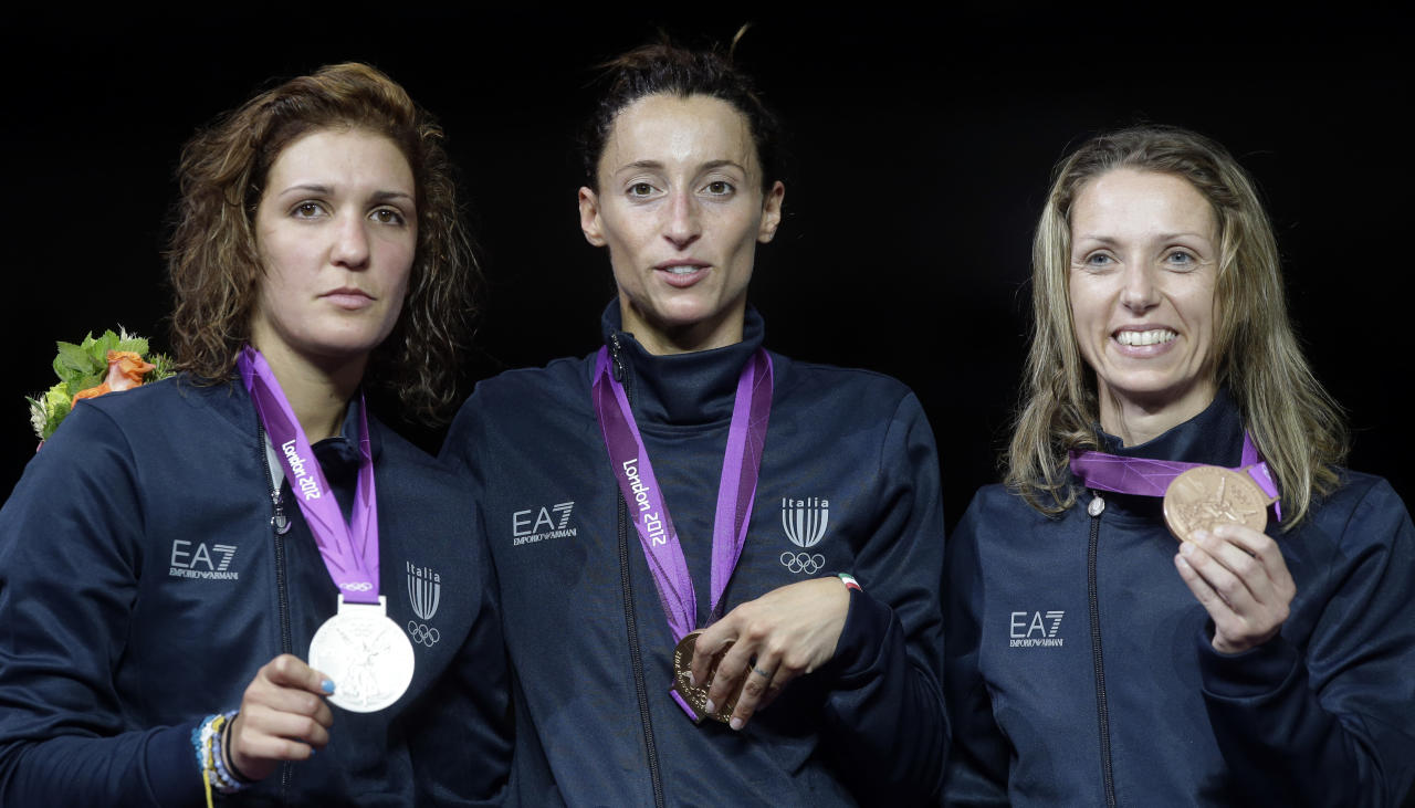 Italy's gold medalist Elisa Di Francisca is flanked by  silver medalist Arianna Errigo, left,  and bronze medallist Valentina Vezzali pose after receiving their medals for fencing at the 2012 Summer Olympics, Saturday, July 28, 2012, in London. (AP Photo/Andrew Medichini)