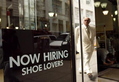 A sign in the window of a retail shoe store advertises for jobs in San Francisco, California