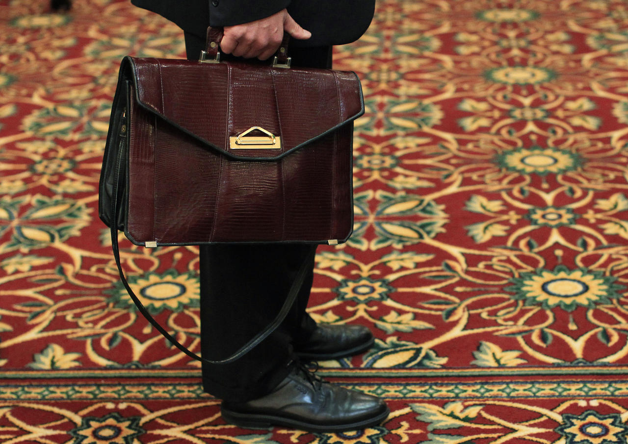 A man holds his briefcase while waiting in line during a job fair in Melville, New York July 19, 2012.  The number of Americans filing new claims for unemployment benefits rebounded last week, returning to levels consistent with only modest job growth after a seasonal quirk caused a sharp drop the prior period.  REUTERS/Shannon Stapleton (UNITED STATES - Tags: BUSINESS EMPLOYMENT)
