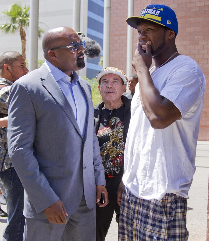 Rap artist 50 Cent, right, talks with Floyd Mayweather Jr.'s advisor, Leonard Ellerbe, after Mayweather turned himself in to begin a 90-day jail term, Friday, June 1, 2012, in Las Vegas. The undefeated five-division champion surrendered Friday before the judge who sentenced him in December for attacking his ex-girlfriend in September 2010 and then allowed him to remain free long enough to headline a May 5 fight.  (AP Photo/Julie Jacobson)