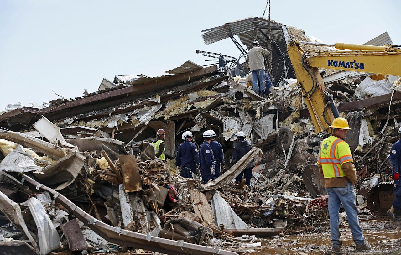 Workers continue going through the debris at the Plaza Towers Elementary School in Moore, Okla., on Tuesday, May 21, 2013. A tornado hit the area on Monday, May 20, 2013. (AP Photo/The Oklahoman, Bryan Terry)