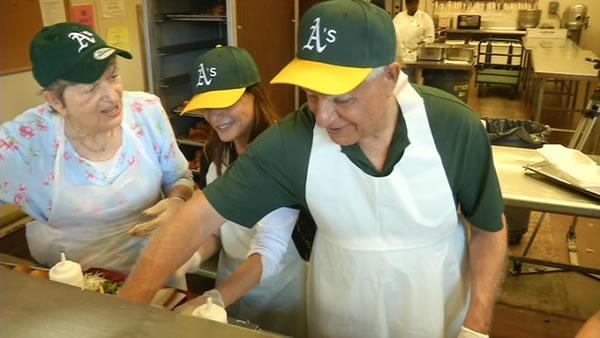 Oakland A's owner Lew Wolff lends a hand